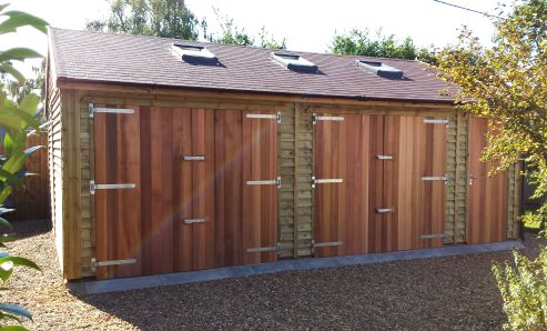 A very attractive garage with cedar double doors, felt tiles, feather edge boarding and 3 x velux windows.