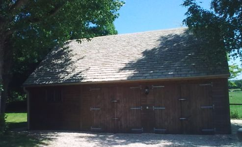 A very attractive Traditional Triple Warwick Buildings Garage stained in Protek Chestnut Wood Protector. Special trusses at 45 degrees are used to construct a roof using Cotswold Slate Tiles